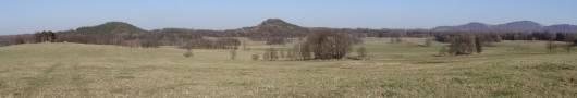 Ostrovní hory Jahodník (378 m n. m.) na obrázku vlevo a Smolný (404 m n. m.) uprostřed. Vpravo v pozadí horský hřeben Sokolského hřbetu. Pohled od západu, z vyvýšeniny jihozápadně od železniční zastávky Kobylá nad Vidnavkou.